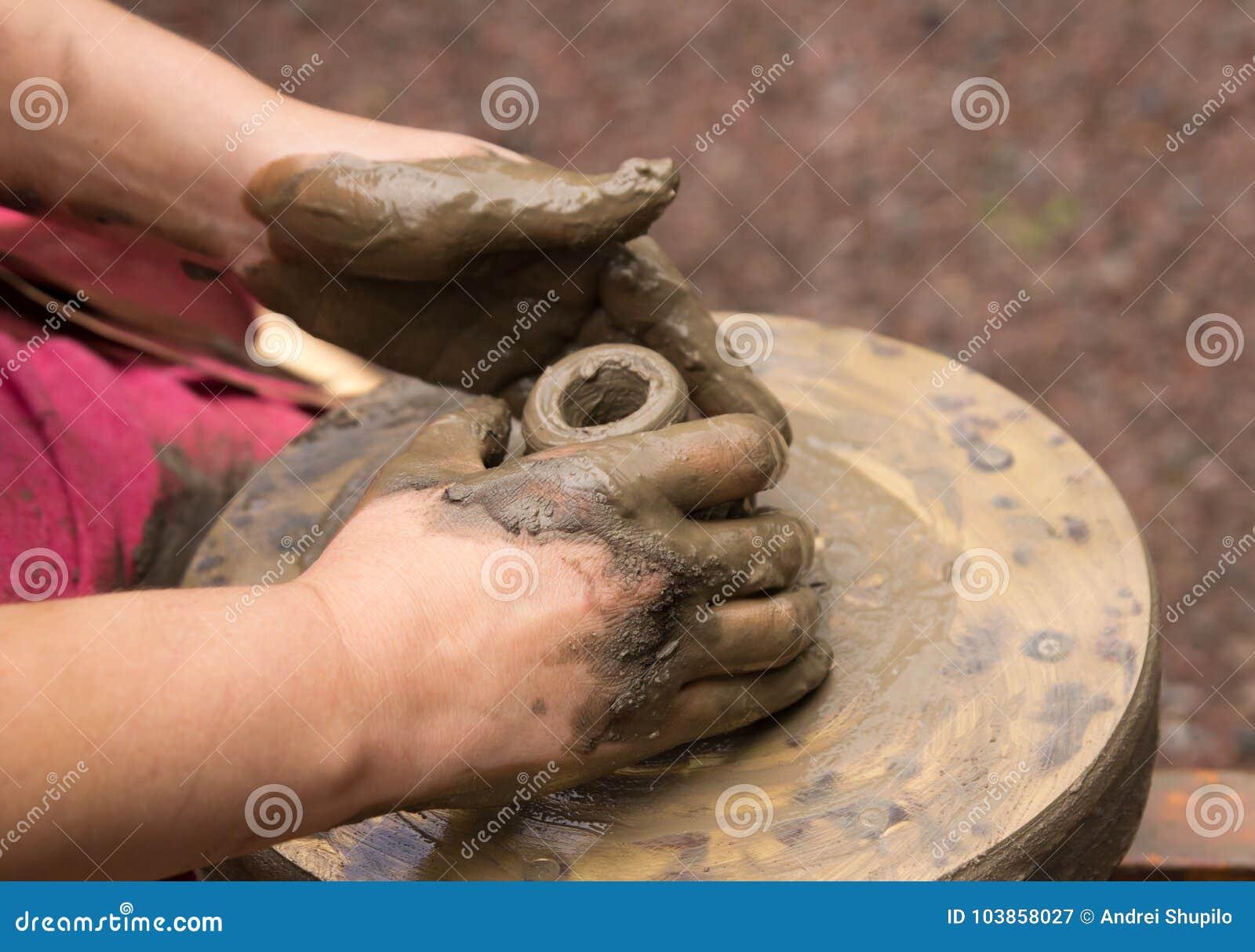 Traînez les mains faisant en argile sur la roue de poterie Le potier effectue sur le bac d argile de roue de poterie