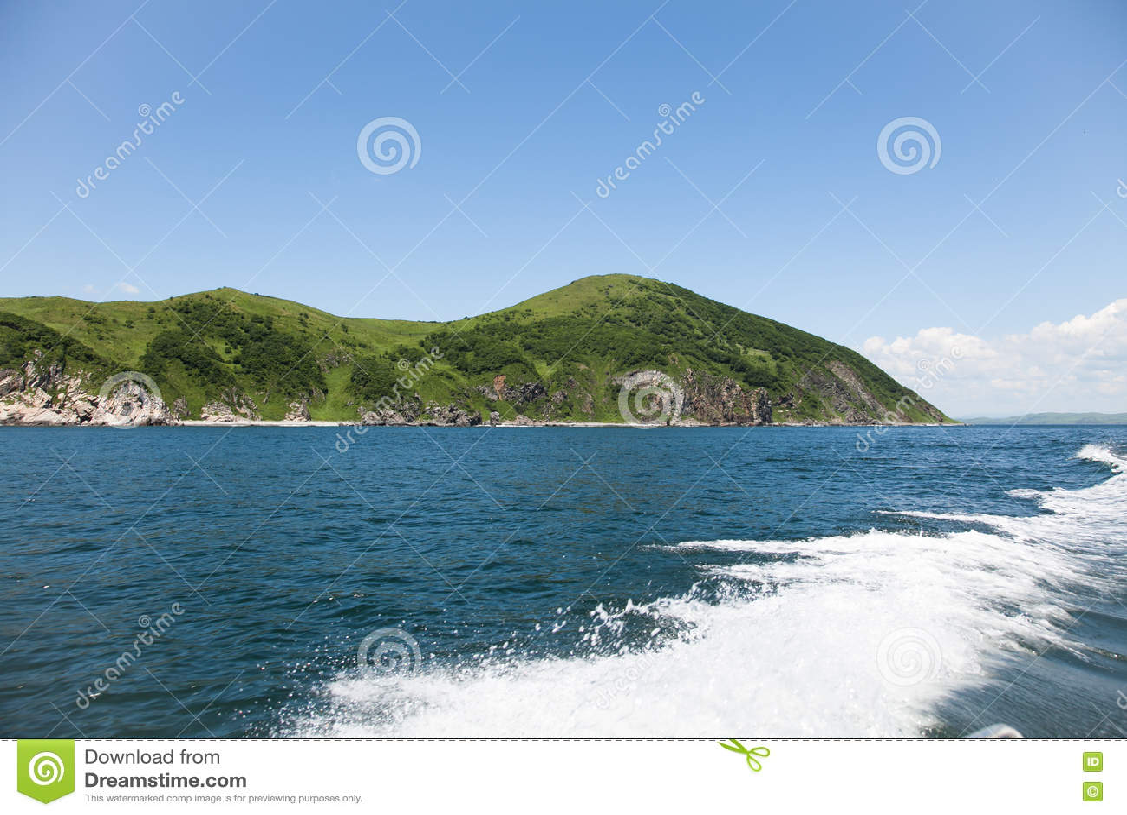 Traînez sur la surface d eau de mer derrière le bateau contre le contexte du terrain accidenté