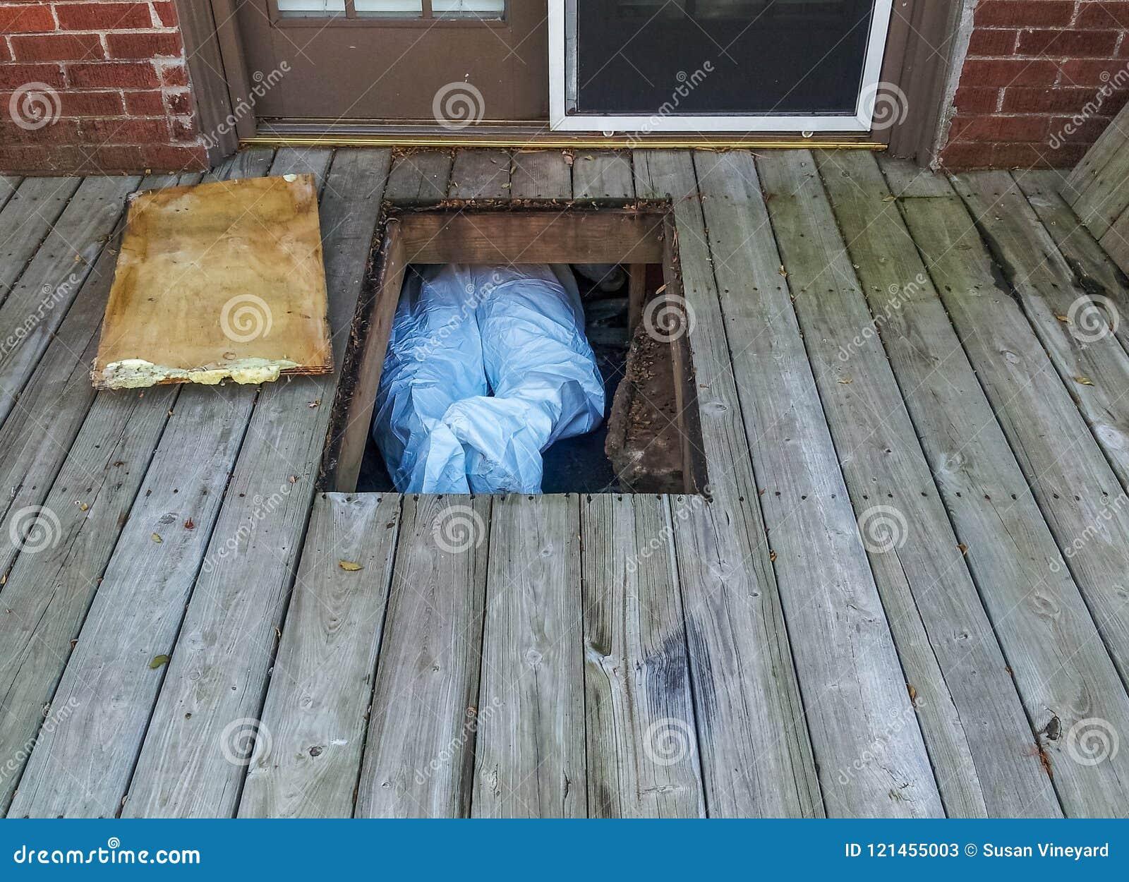 Trabajador con el traje protector crawing debajo de casa del crawlspace por debajo una cubierta de madera - solamente sus piernas