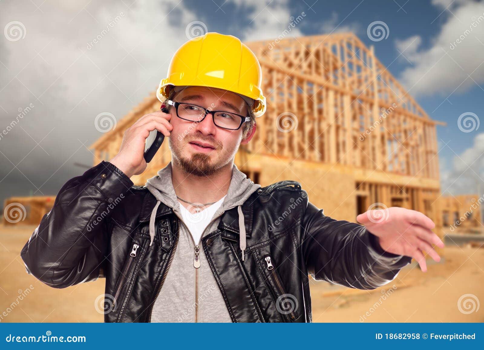 Trabajador de construcción joven en el teléfono en el sitio de la casa