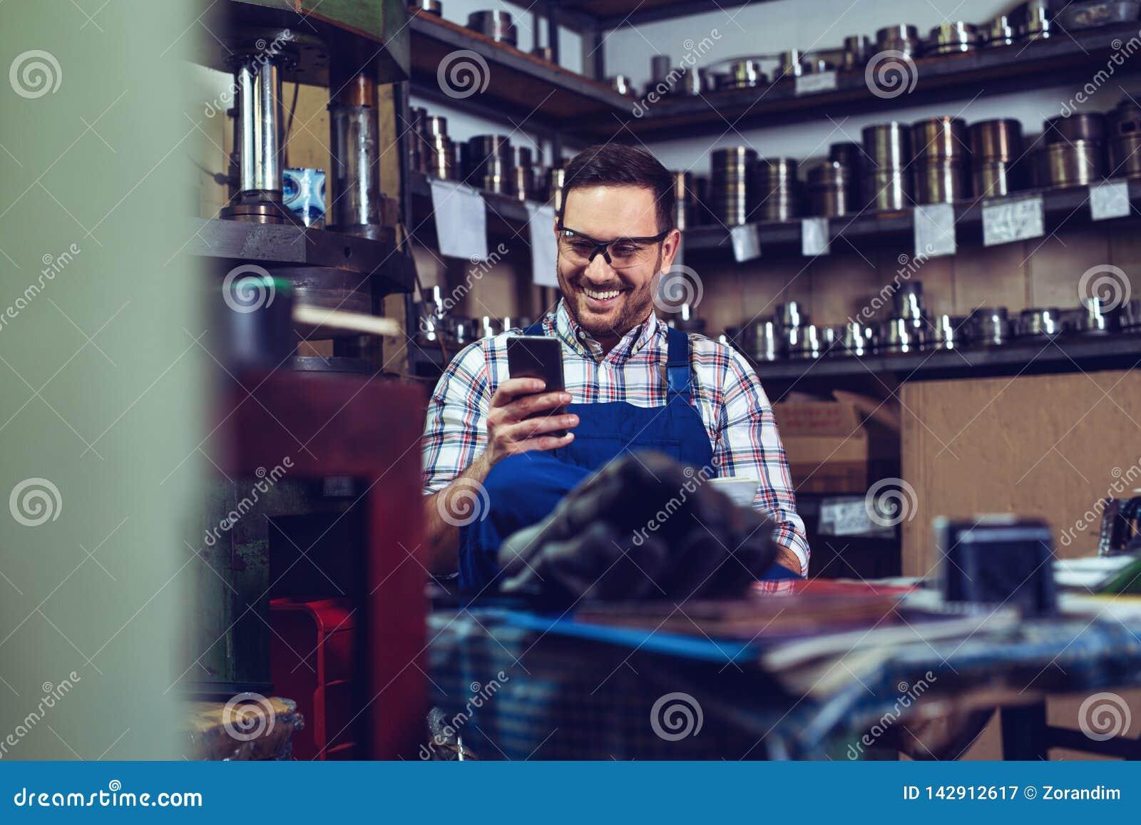 Trabajador de sexo masculino hermoso de la metalurgia en una rotura rápida en instalaciones del almacenamiento