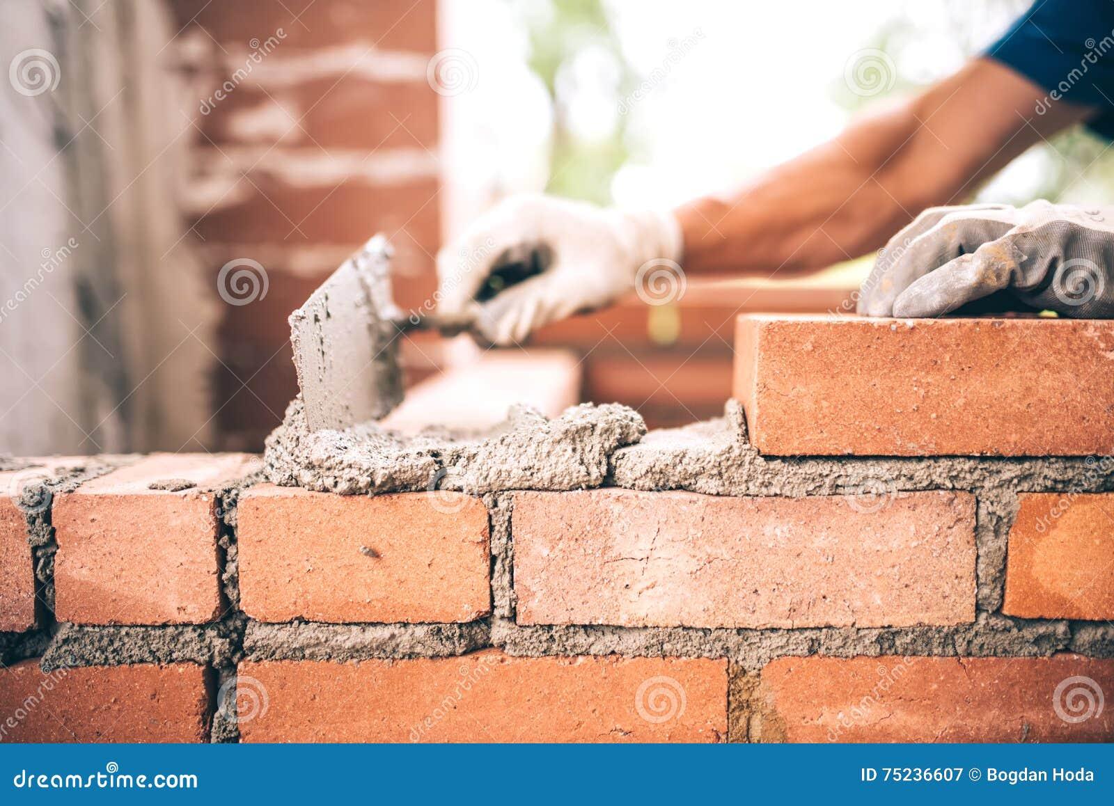 Trabajador del albañil que instala la albañilería del ladrillo en la pared exterior con el cuchillo de masilla de la paleta