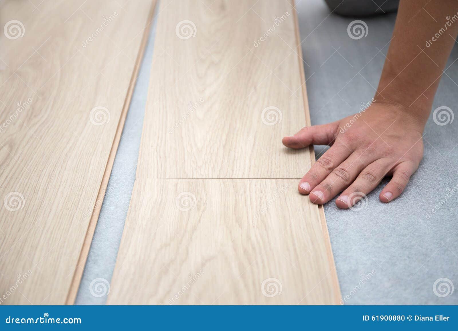 Trabajador del carpintero que instala el suelo laminado en el cuarto