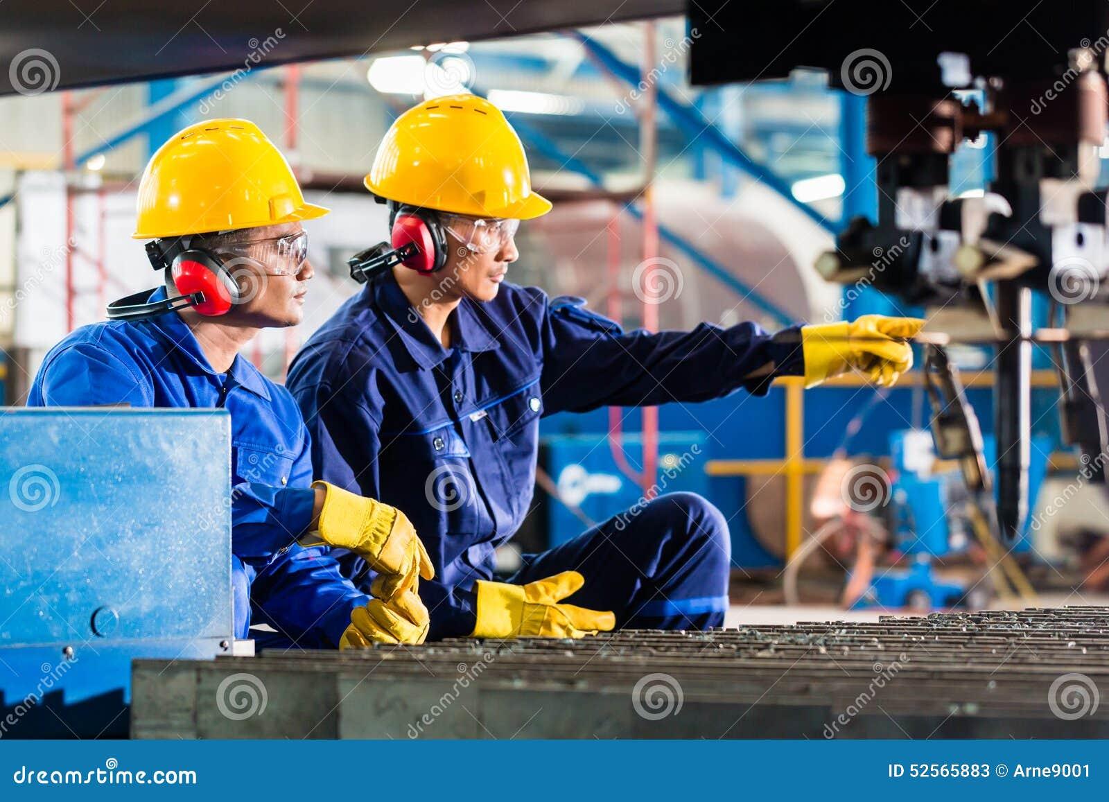 Trabajador en fábrica en la máquina para corte de metales industrial