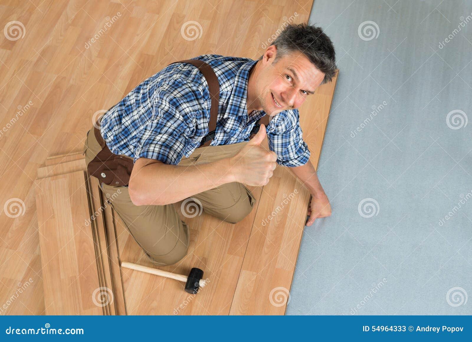 Trabajador feliz que monta el nuevo piso laminado