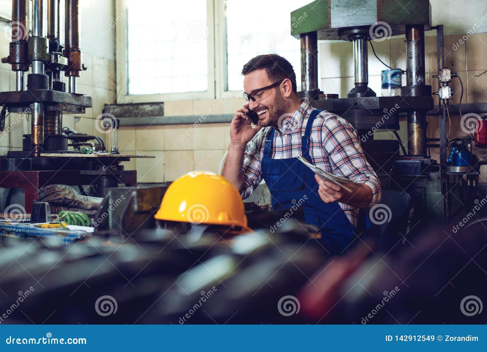 Trabajador hermoso que habla en el teléfono con sus compañeros de trabajo