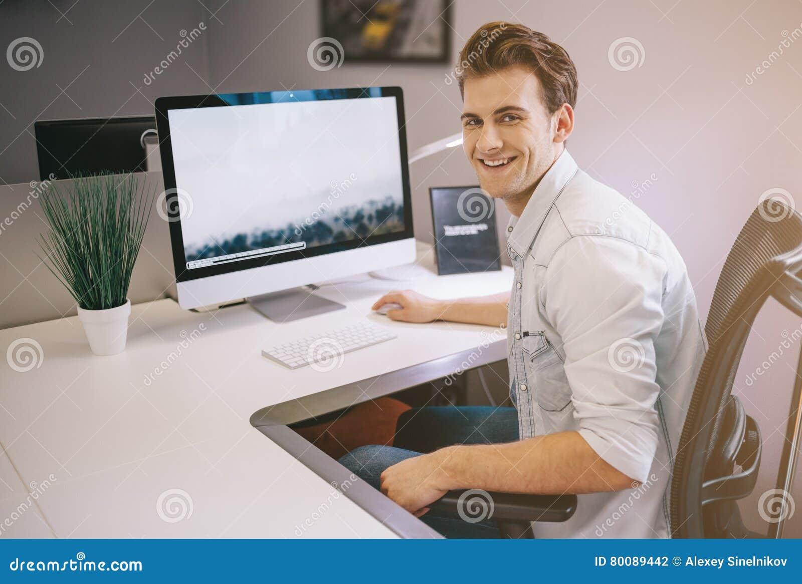 Trabajador joven que se sienta en una oficina en el for Explique que es una oficina