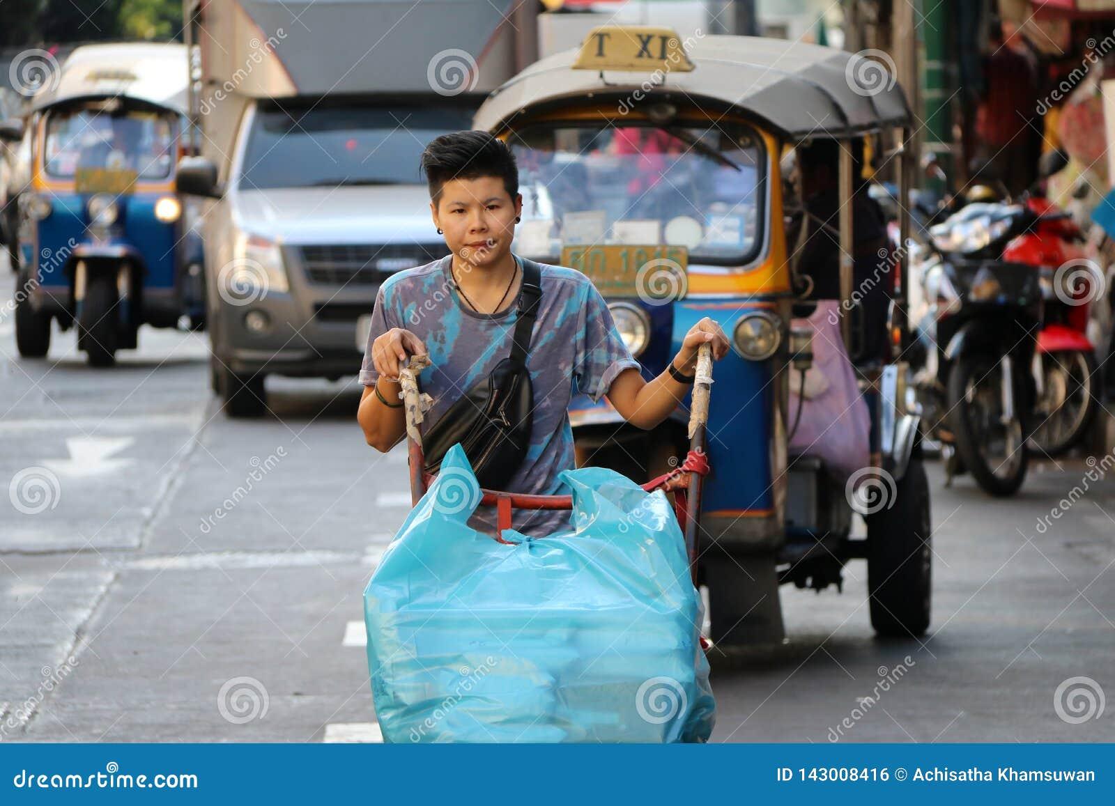 Trabajador que empuja la carretilla de dos ruedas en el camino a la mercancía de la entrega en la ciudad comercial de Sampheng, B