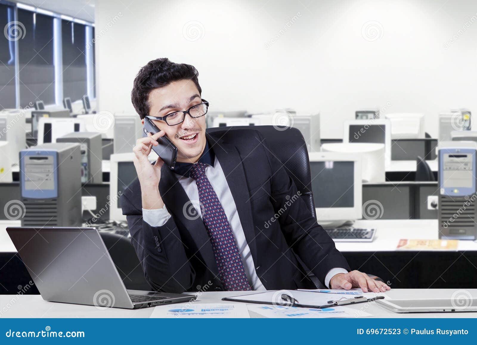 Trabajador que habla en el tel fono m vil en sitio de la for La oficina telefono