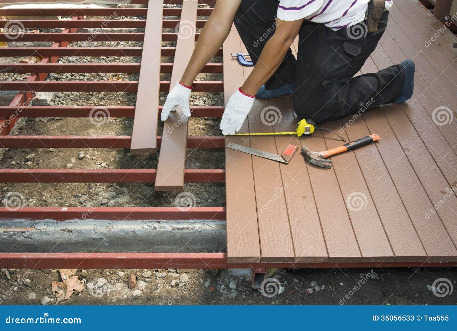trabajador que instala el piso de madera para el patio