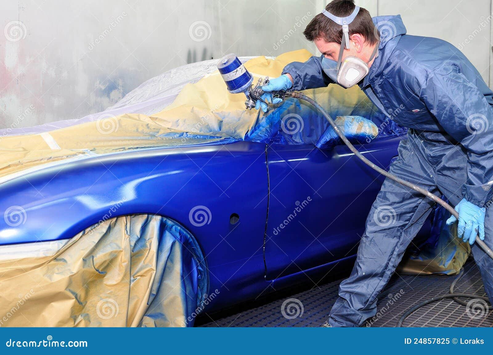 Trabajador que pinta un coche azul.