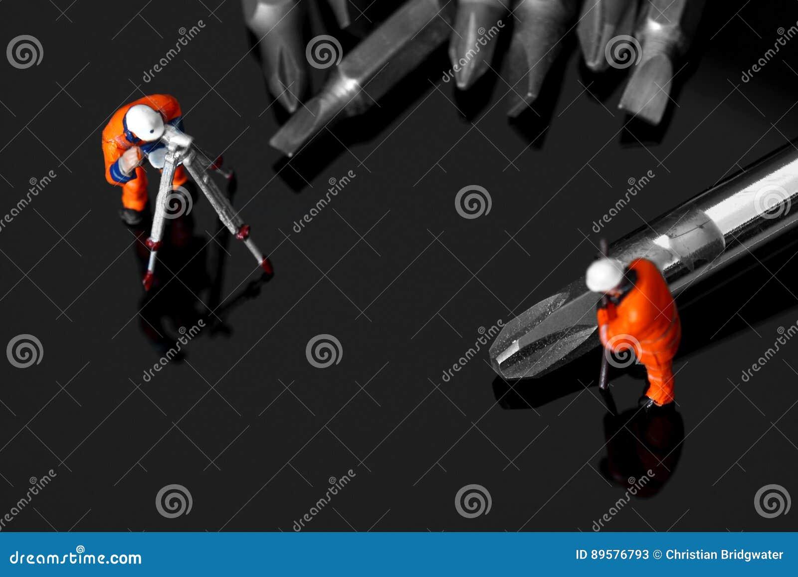Trabajadores de construcción modelo con un destornillador y los pedazos