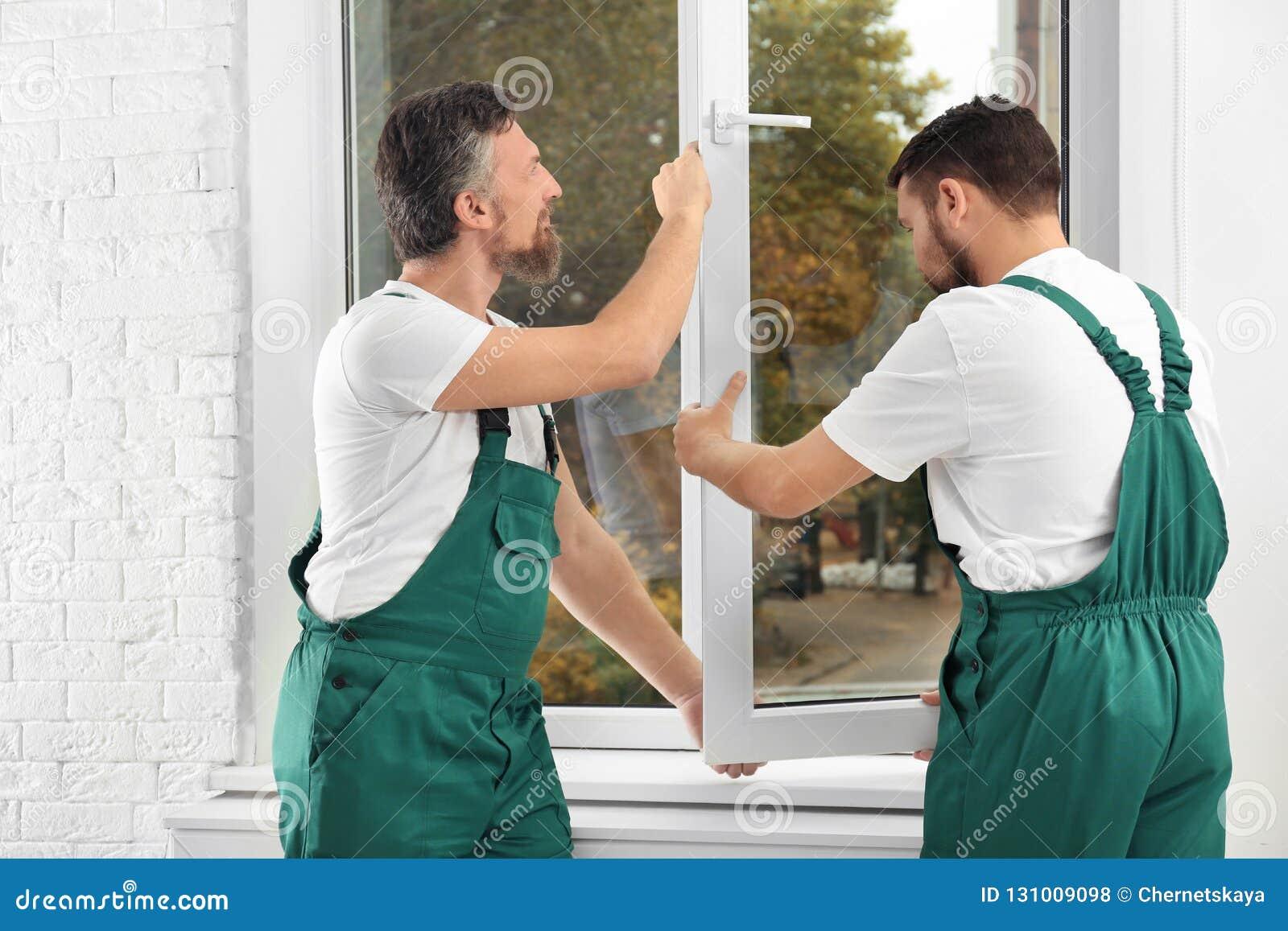 Trabajadores de construcción que instalan la nueva ventana