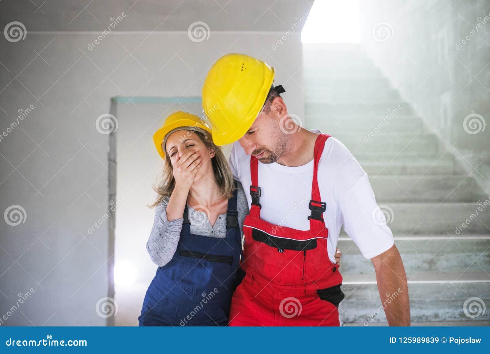 Trabajadores De La Mujer Y Del Hombre Que Sofocan En El Emplazamiento De La Obra Imagen De Archivo Imagen De Hombre Sofocan 125989839