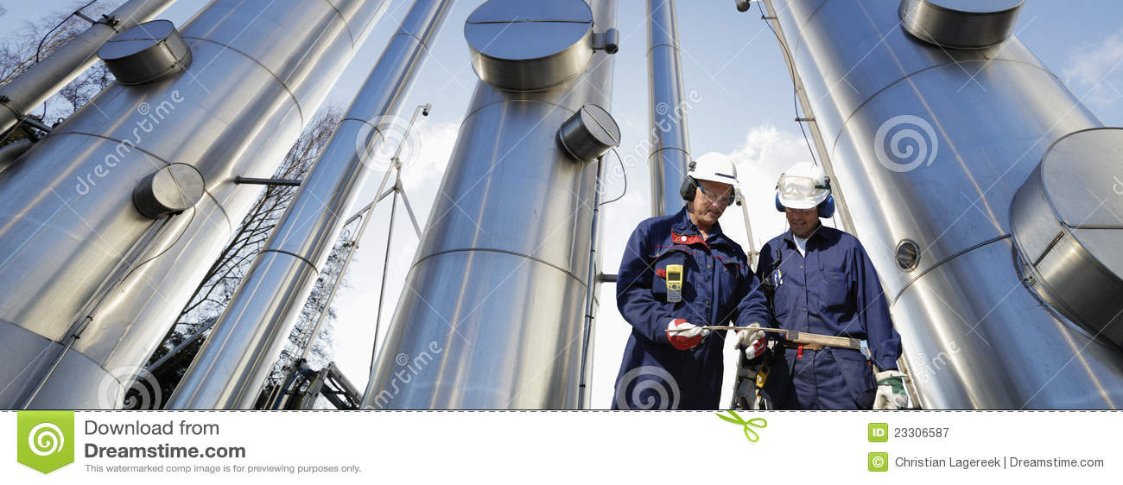 Trabajadores de petróleo y del gas con las tuberías