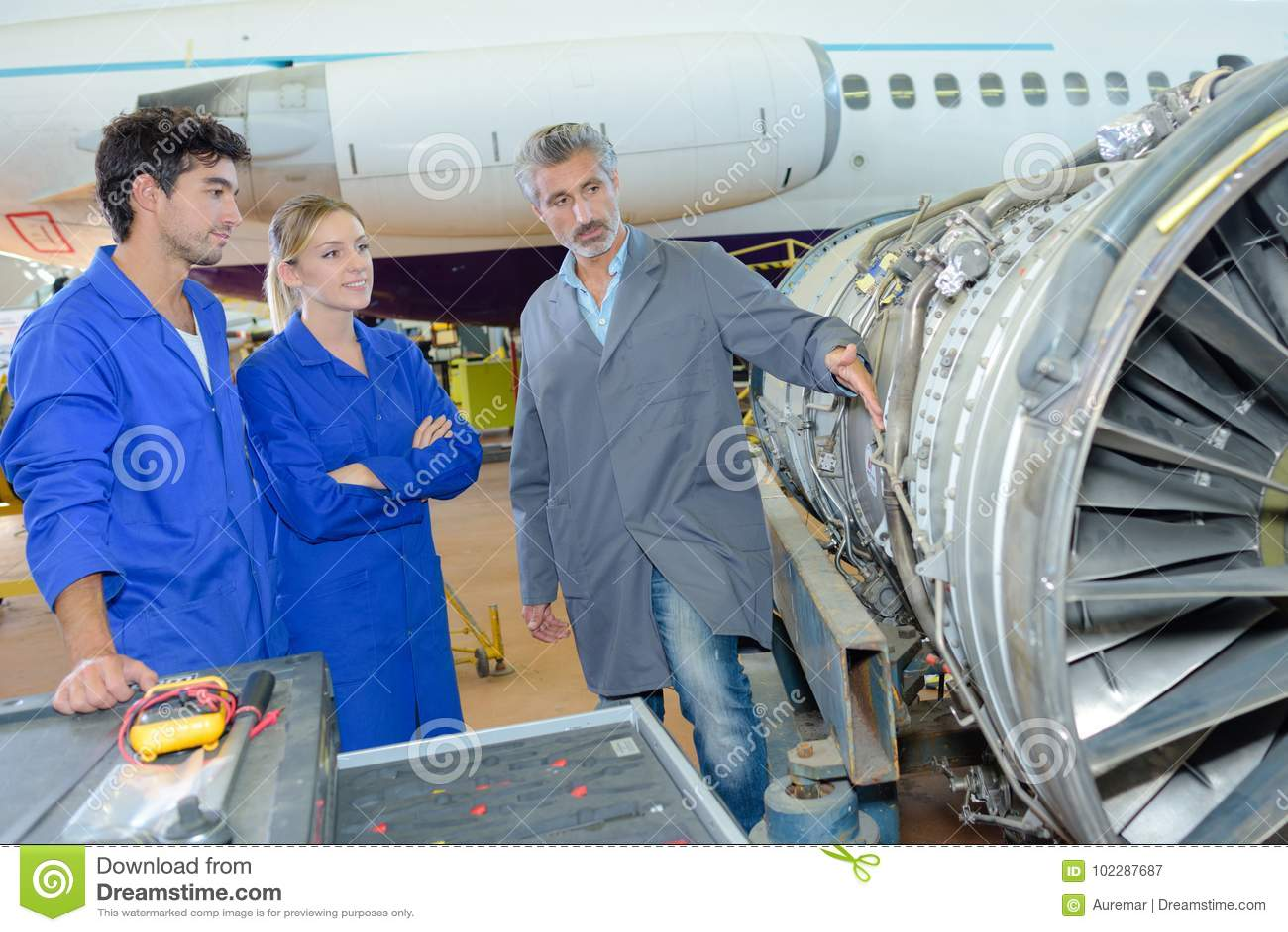 Trabajadores del aeropuerto con el aeroplano en fondo
