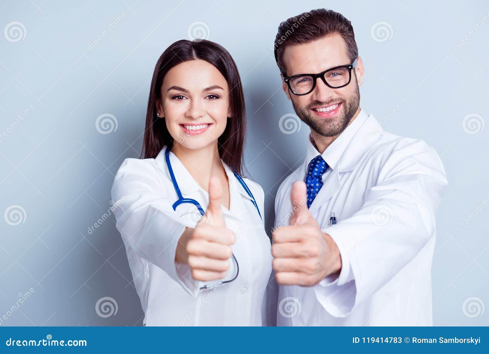 Trabajadores felices del médico Retrato de dos doctores en las capas blancas y
