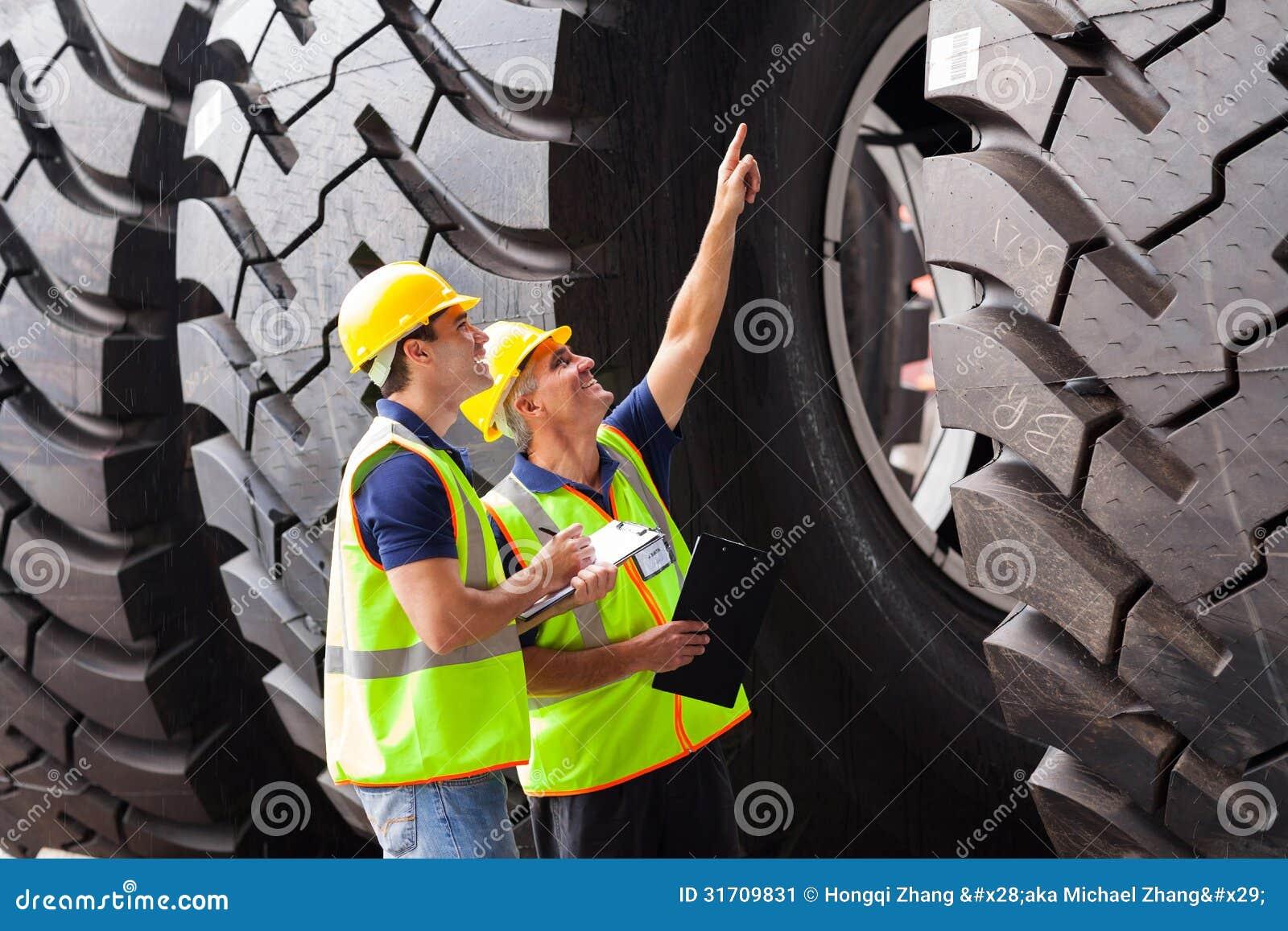 Trabajadores que comprueban los neumáticos