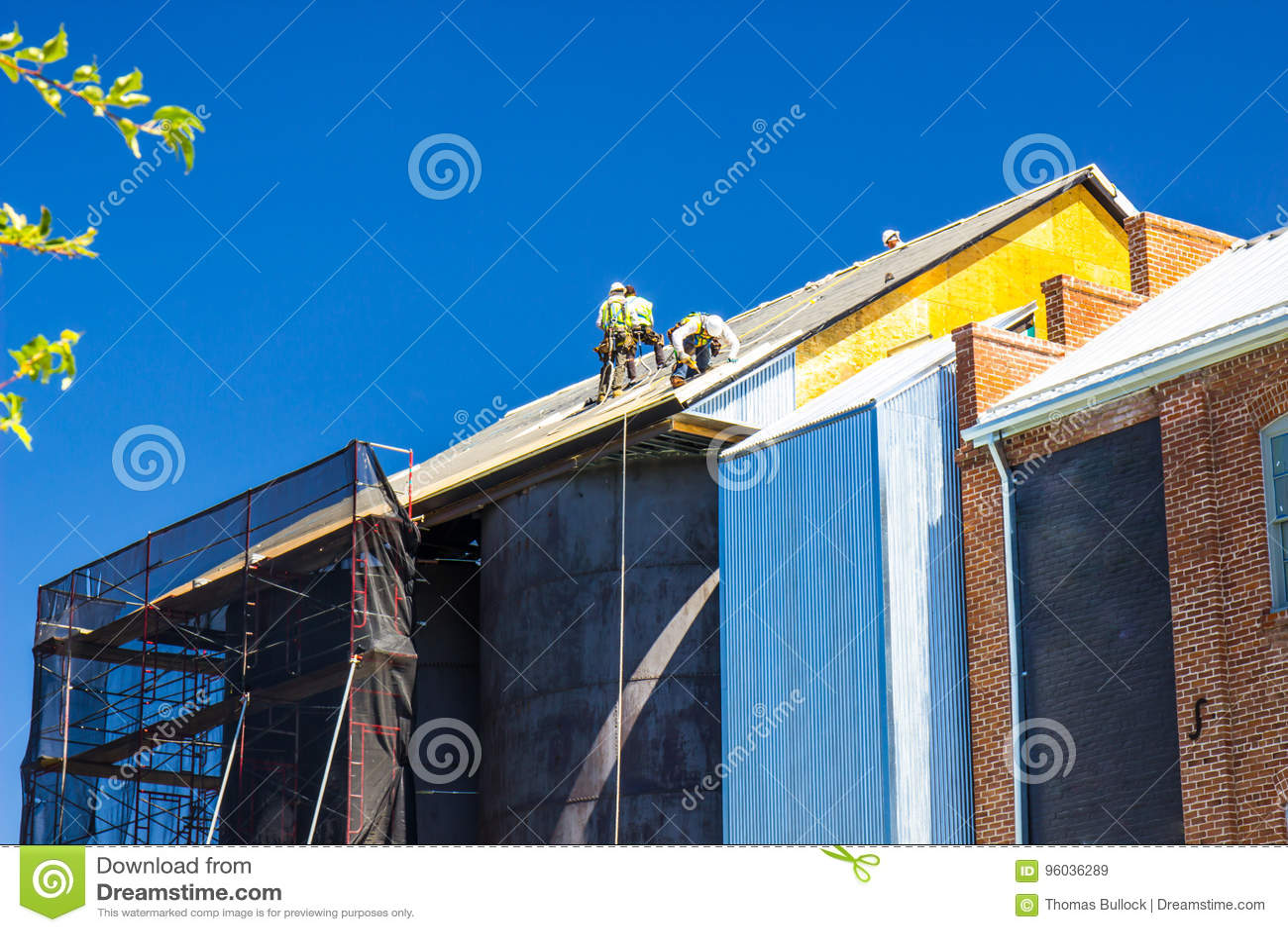 Trabajadores que instalan los materiales de techumbre sobre los tanques de almacenamiento del vintage
