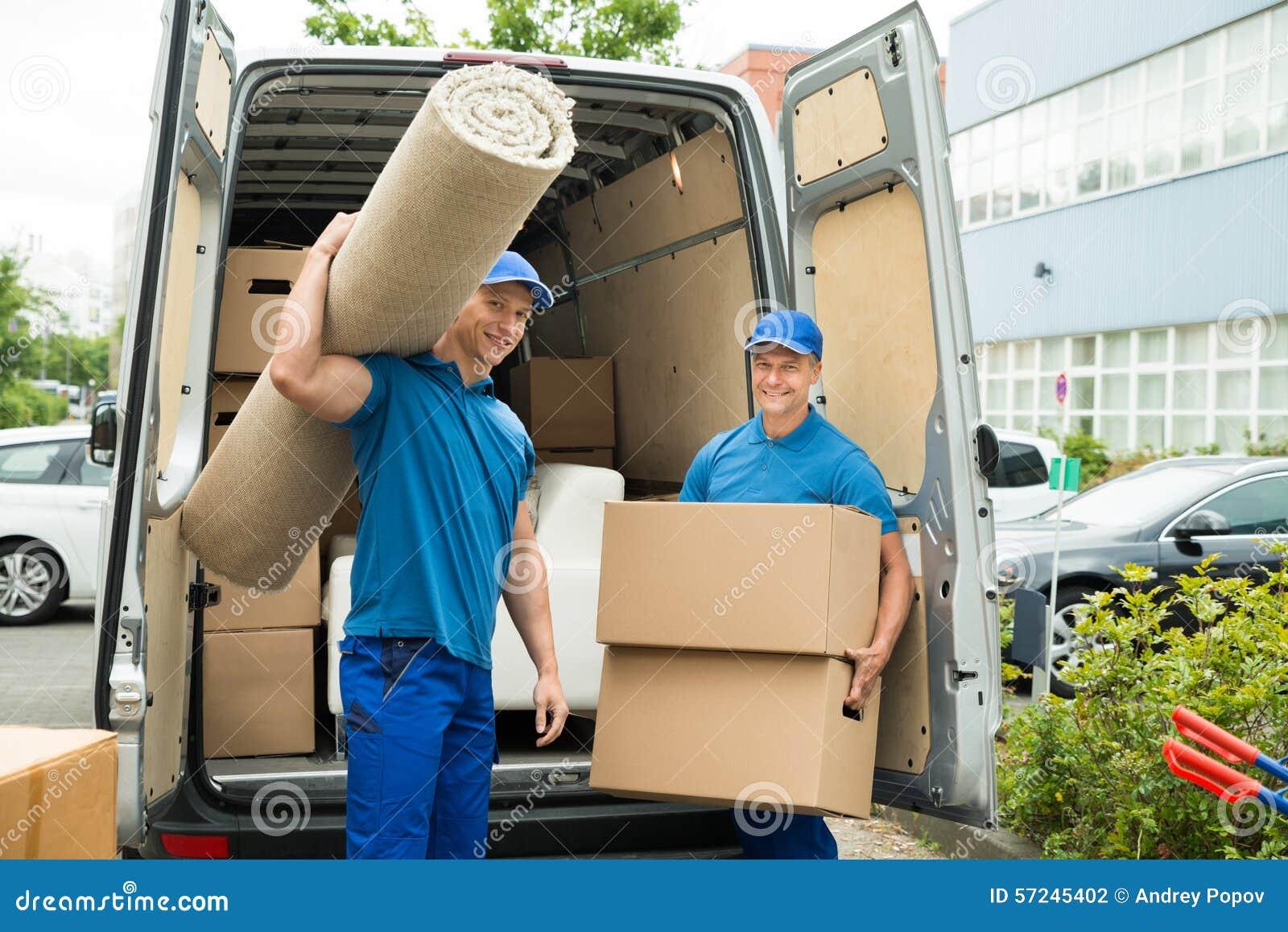 Trabajadores que llevan las cajas de la alfombra y de cartón