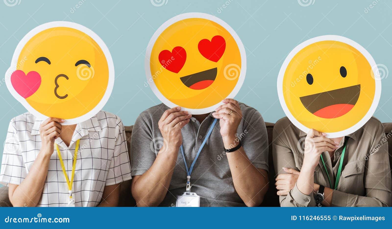 Trabajadores que sostienen emojis felices de la cara