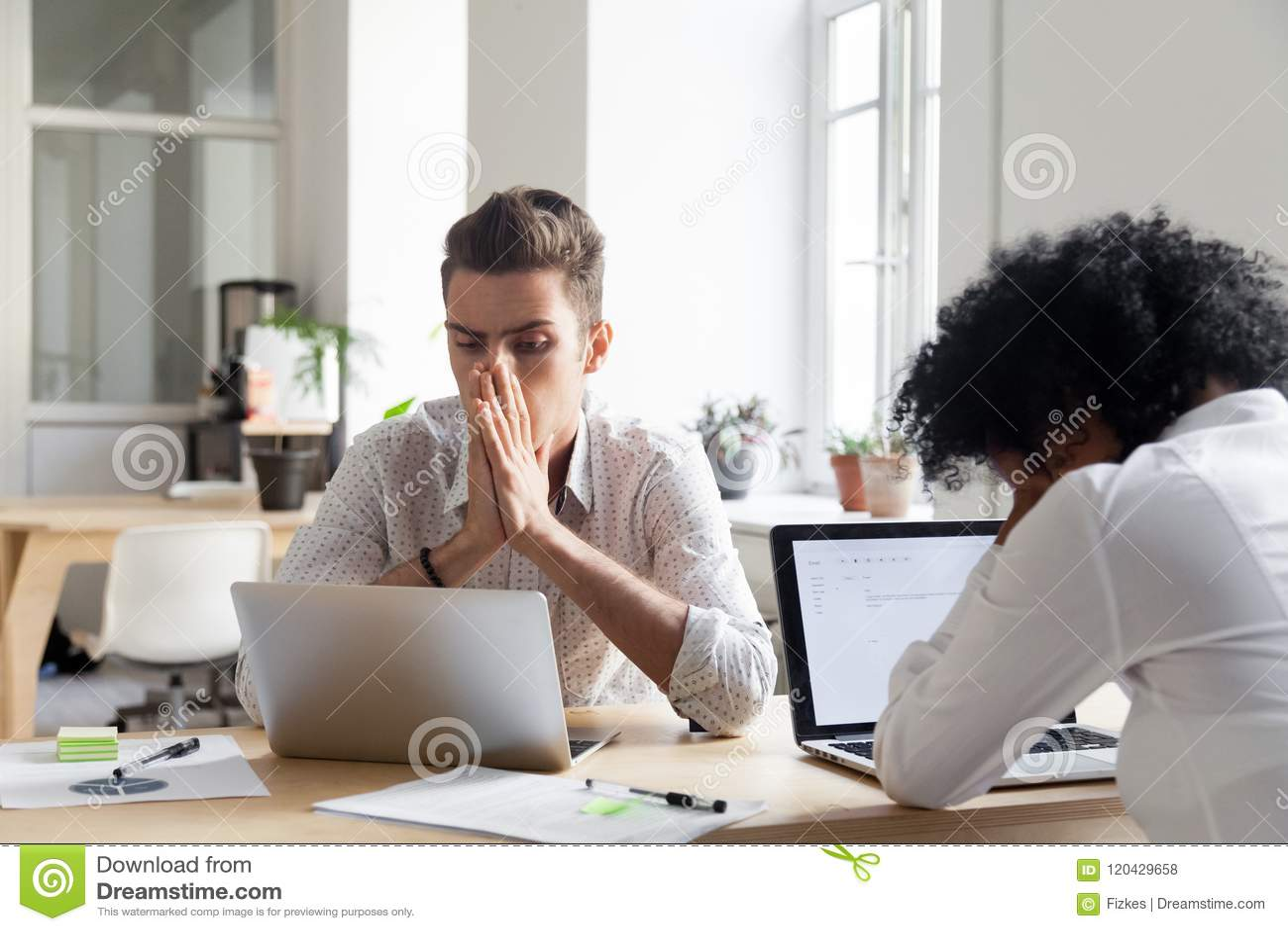 Trabajadores subrayados que leen noticias de la quiebra de compañía en línea