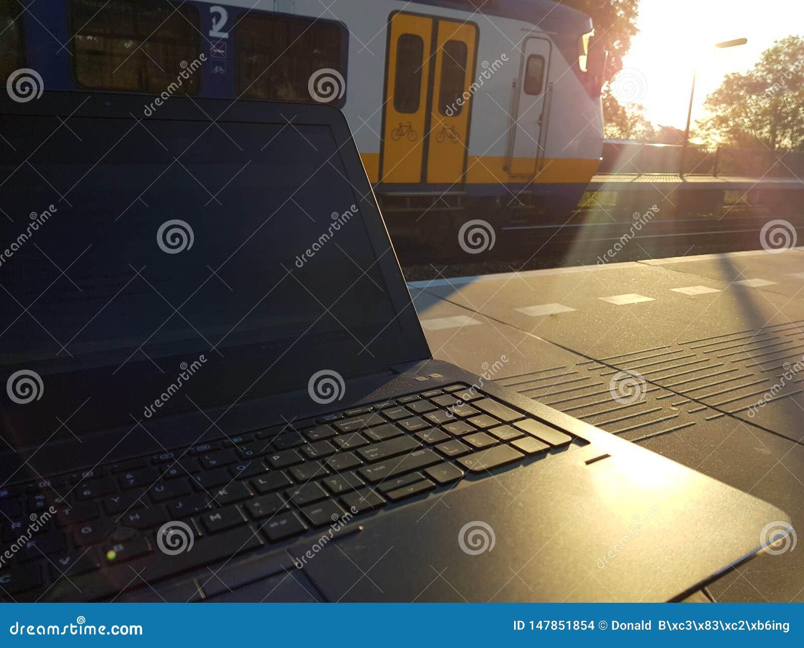 Trabajando en el ordenador portátil mientras que espera en la plataforma tren, maximice la productividad