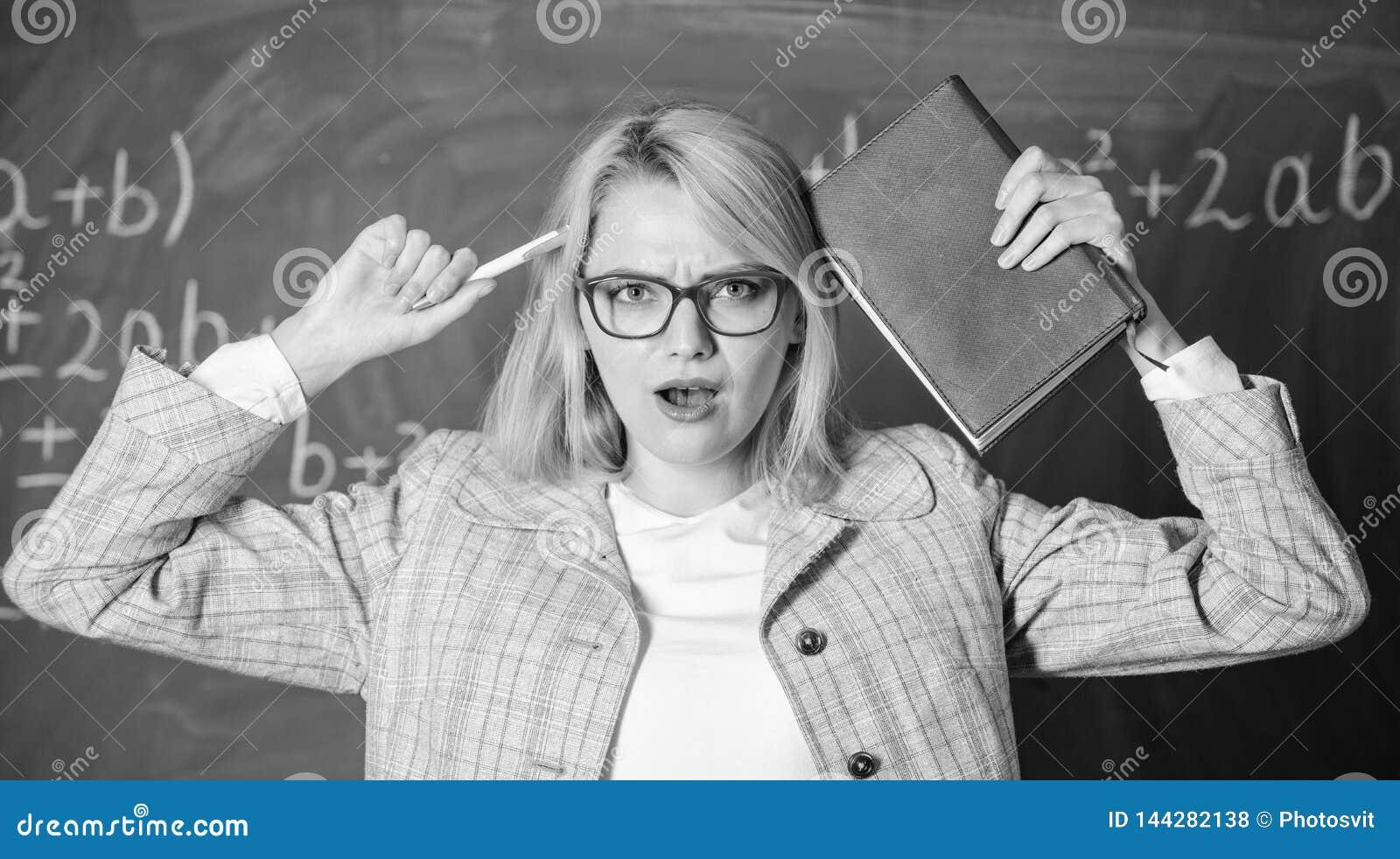 Trabaje demasiado y falta de ayuda que conduce al profesor de la profesión Mujer del profesor con el fondo de la pizarra del libr