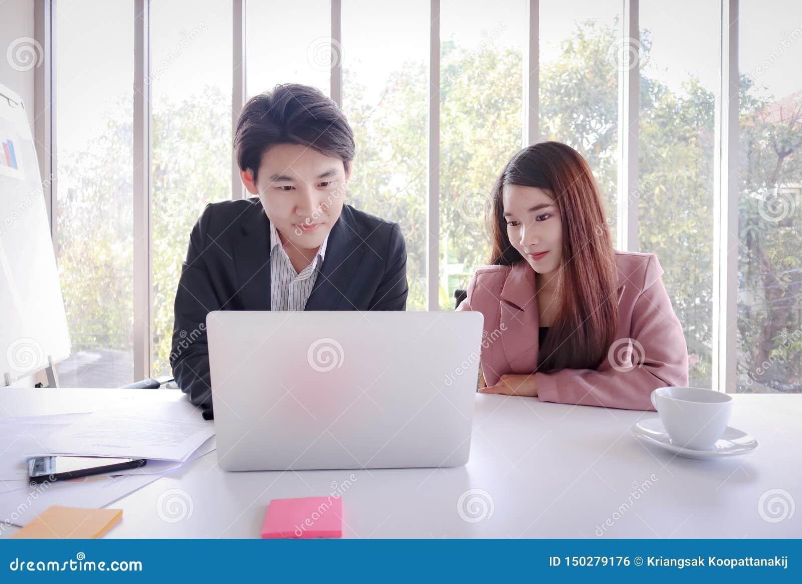 Trabajo asiático joven del hombre de negocios con el ordenador portátil en la oficina