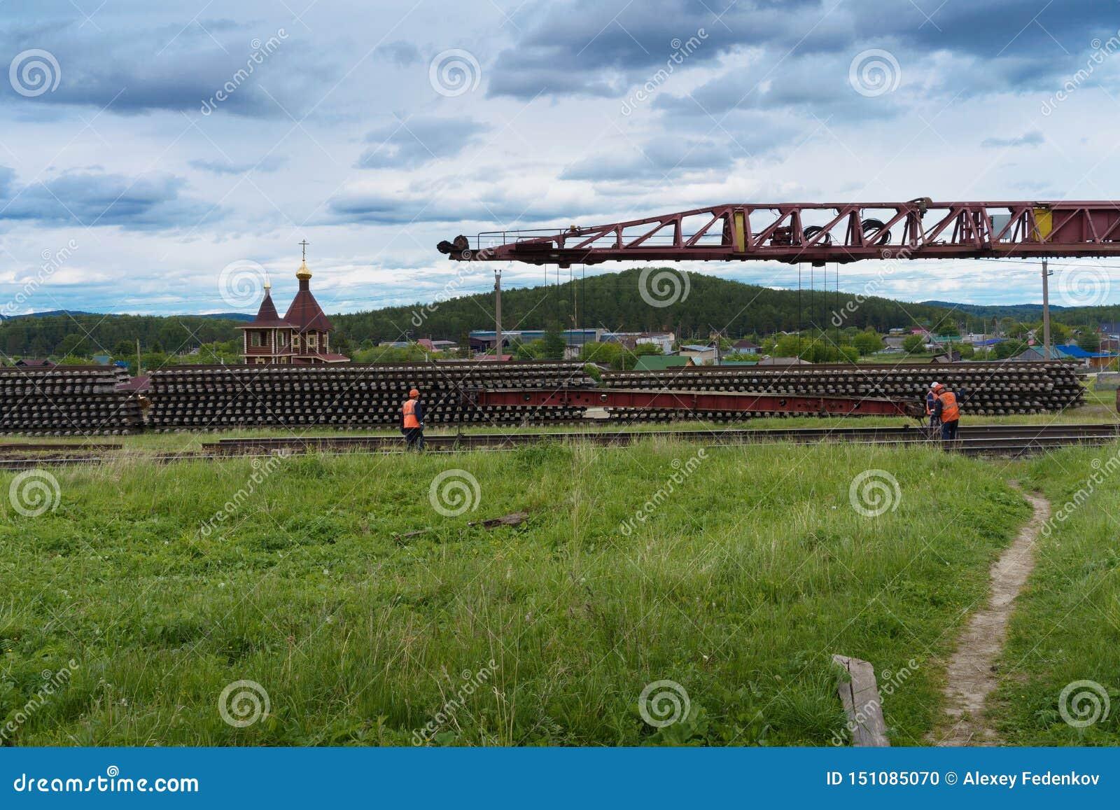 Trabajo de la reparación sobre el camino ferroviario en el campo en Rusia