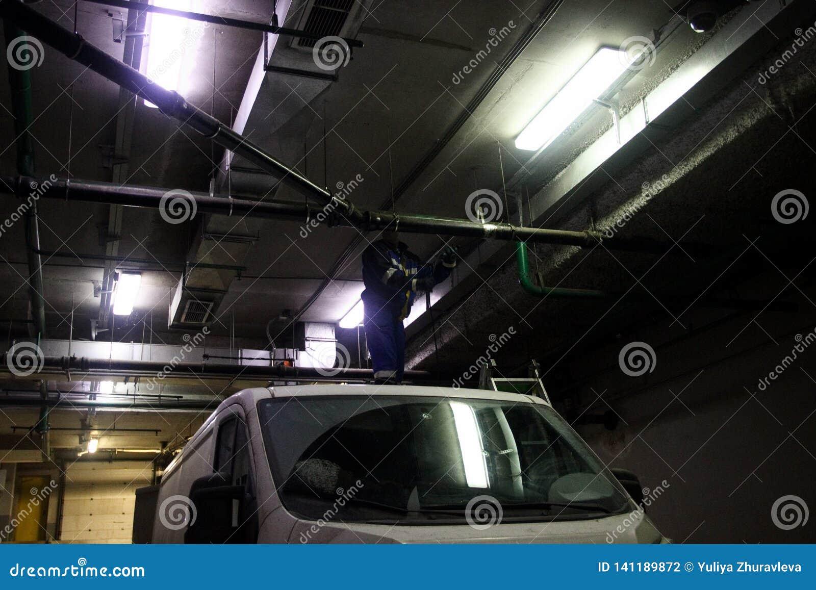 Trabajo de limpio industrial de las aguas residuales, fontanería, ventilación en base del coche en el edificio profesional