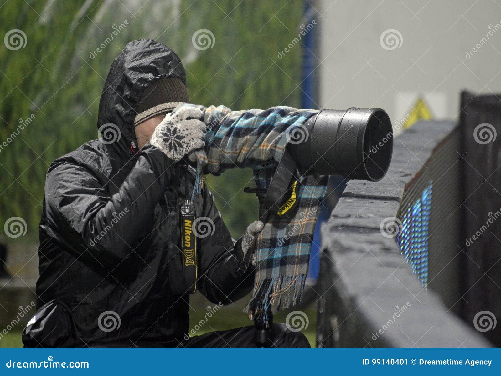 Trabajo del periodista fotográfico en malas condiciones atmosféricas