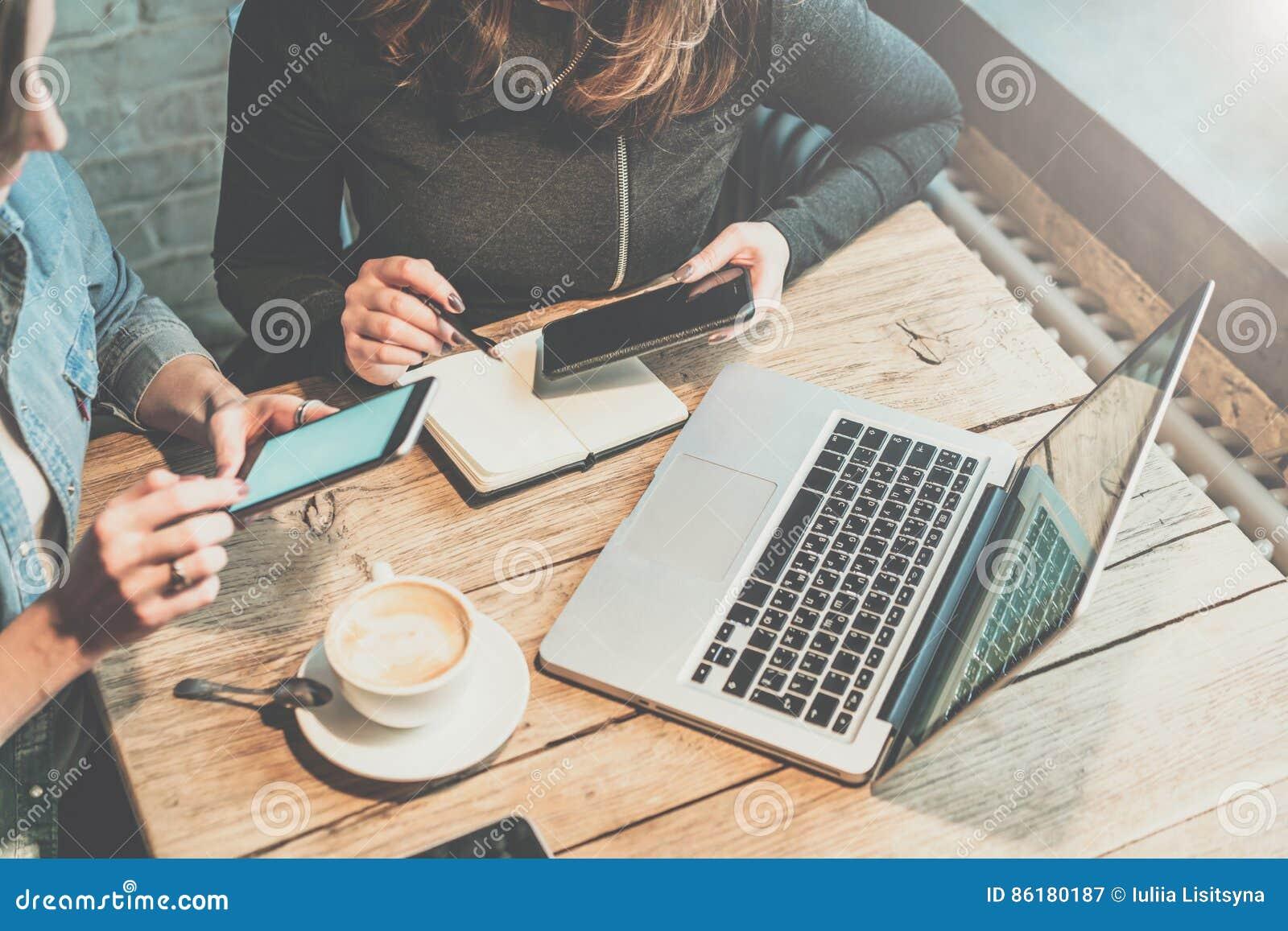 Trabajo en equipo Dos empresarias jovenes que se sientan en la tabla en la cafetería, mirada en su pantalla del smartphone y disc