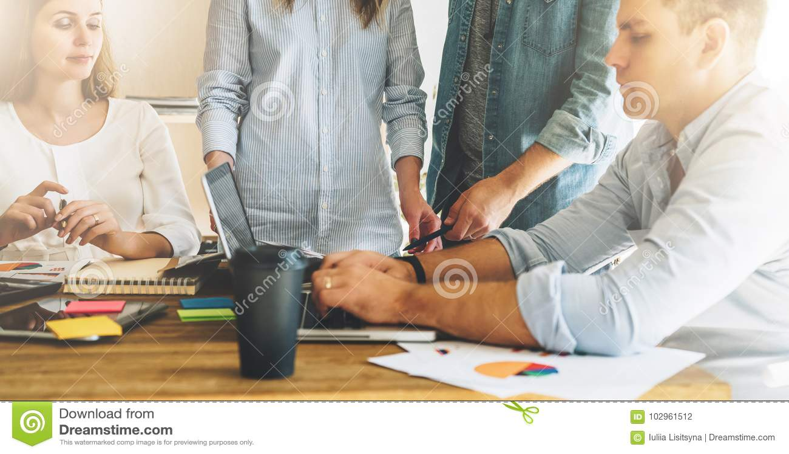 Trabajo en equipo, intercambio de ideas El grupo de empresarios jovenes trabaja junto en oficina en la tabla, leyendo los documen