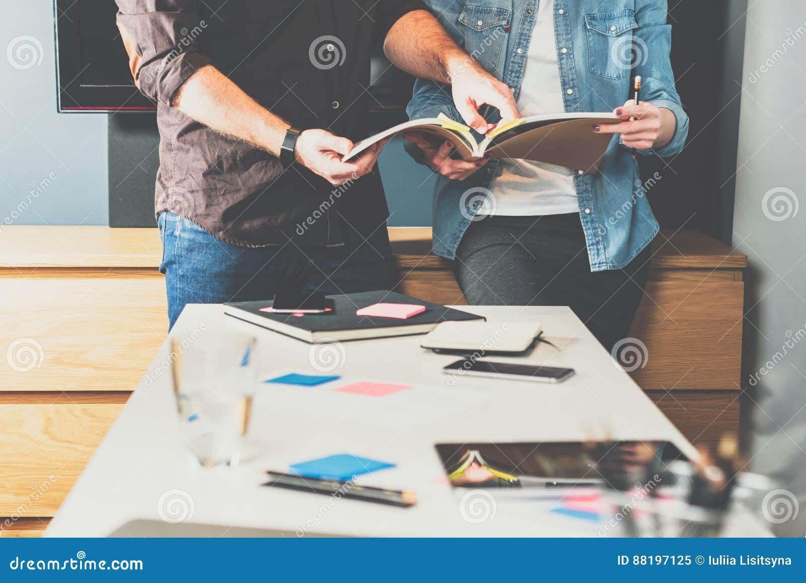 Trabajo en equipo Mujer y hombre de negocios de negocios joven que se colocan en la tabla y la mirada en directorio