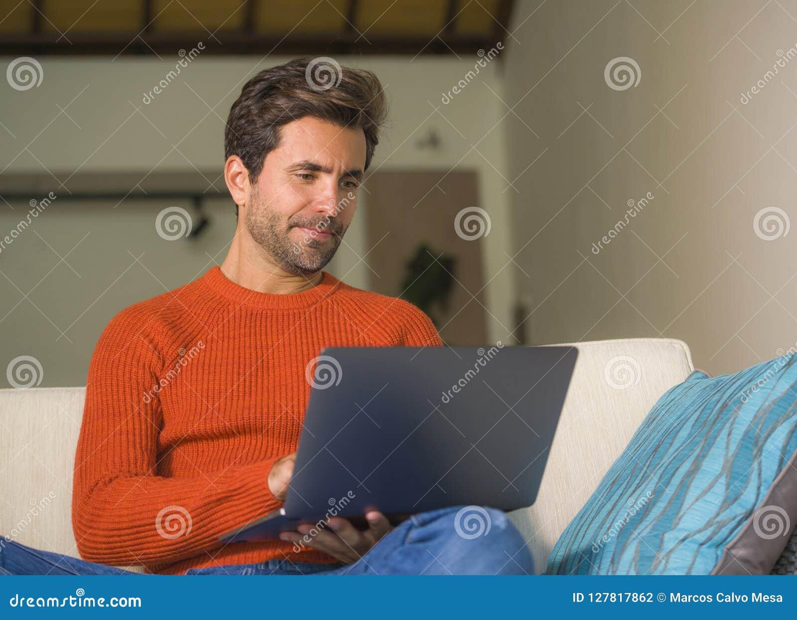Trabajo feliz y atractivo joven del hombre relajado con el ordenador portátil en la sala de estar moderna del apartamento que se