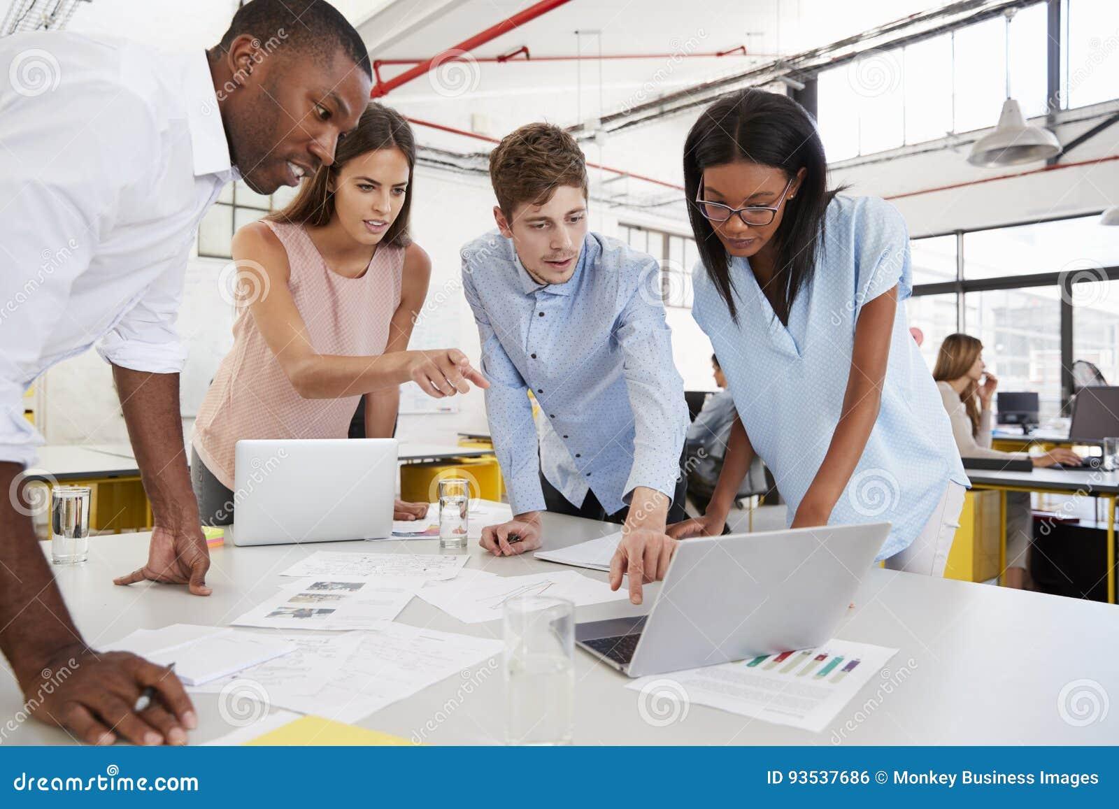 Trabajo joven del equipo del negocio que se coloca en el escritorio en una oficina ocupada