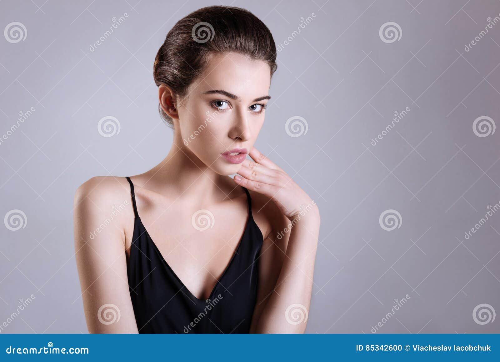 Actitud estándar La chica joven magnética blanda que pega una actitud  mientras que se inclina en una de sus manos y que lleva la seda negra remata 1b1571574e