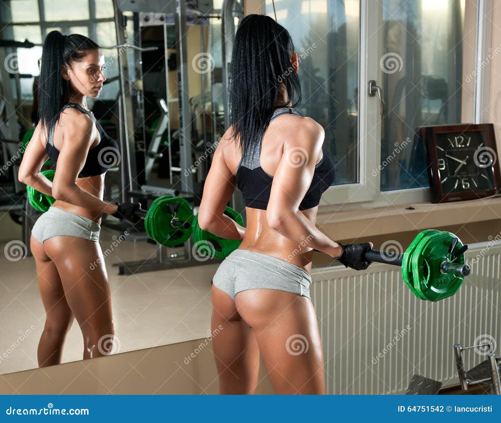 Trabajo moreno magn fico en sus m sculos en un gimnasio for Espejo que no invierte la imagen