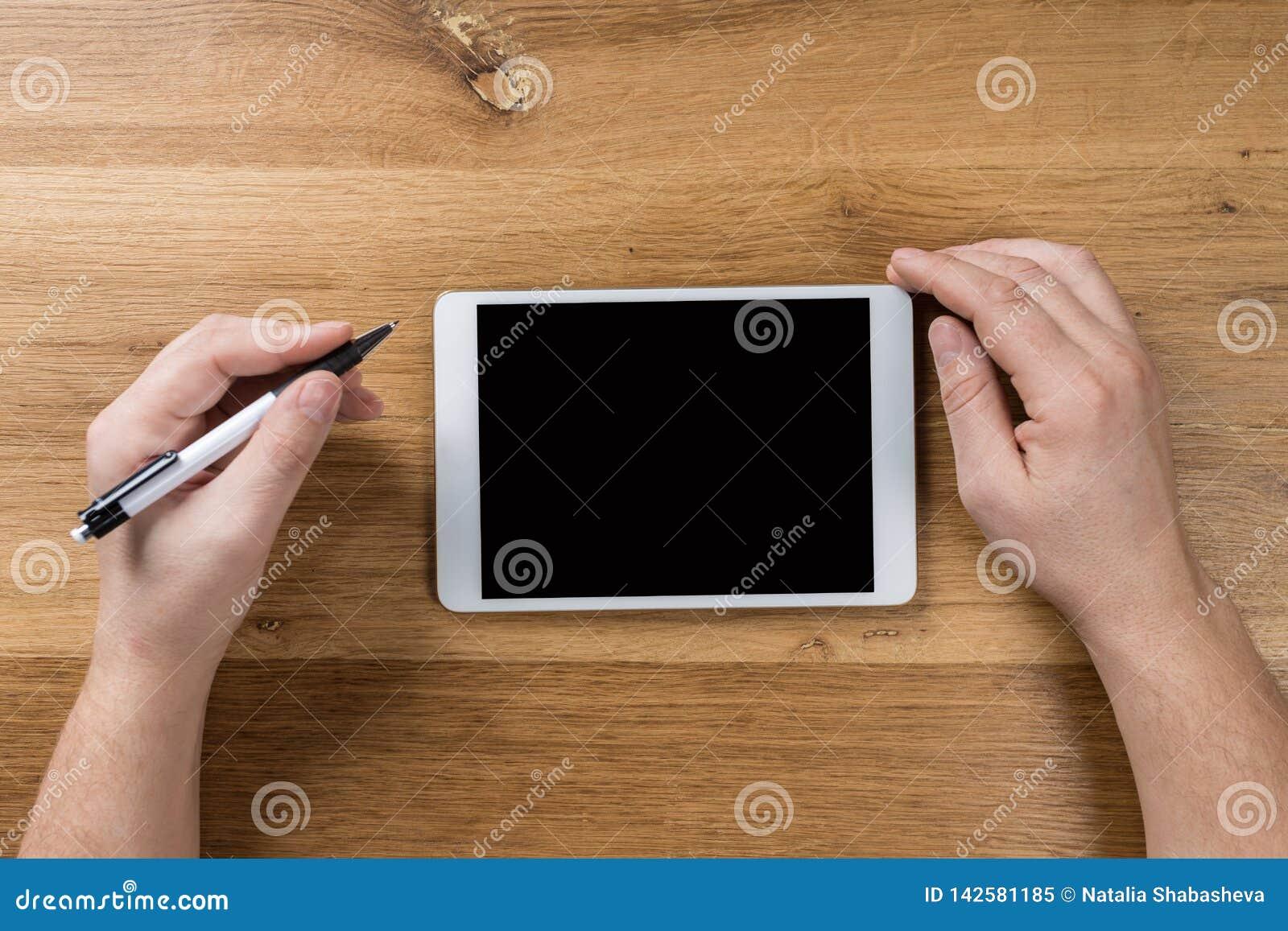 Trabajos del hombre usando los dispositivos digitales Sobre vista del espacio de trabajo de escritorio