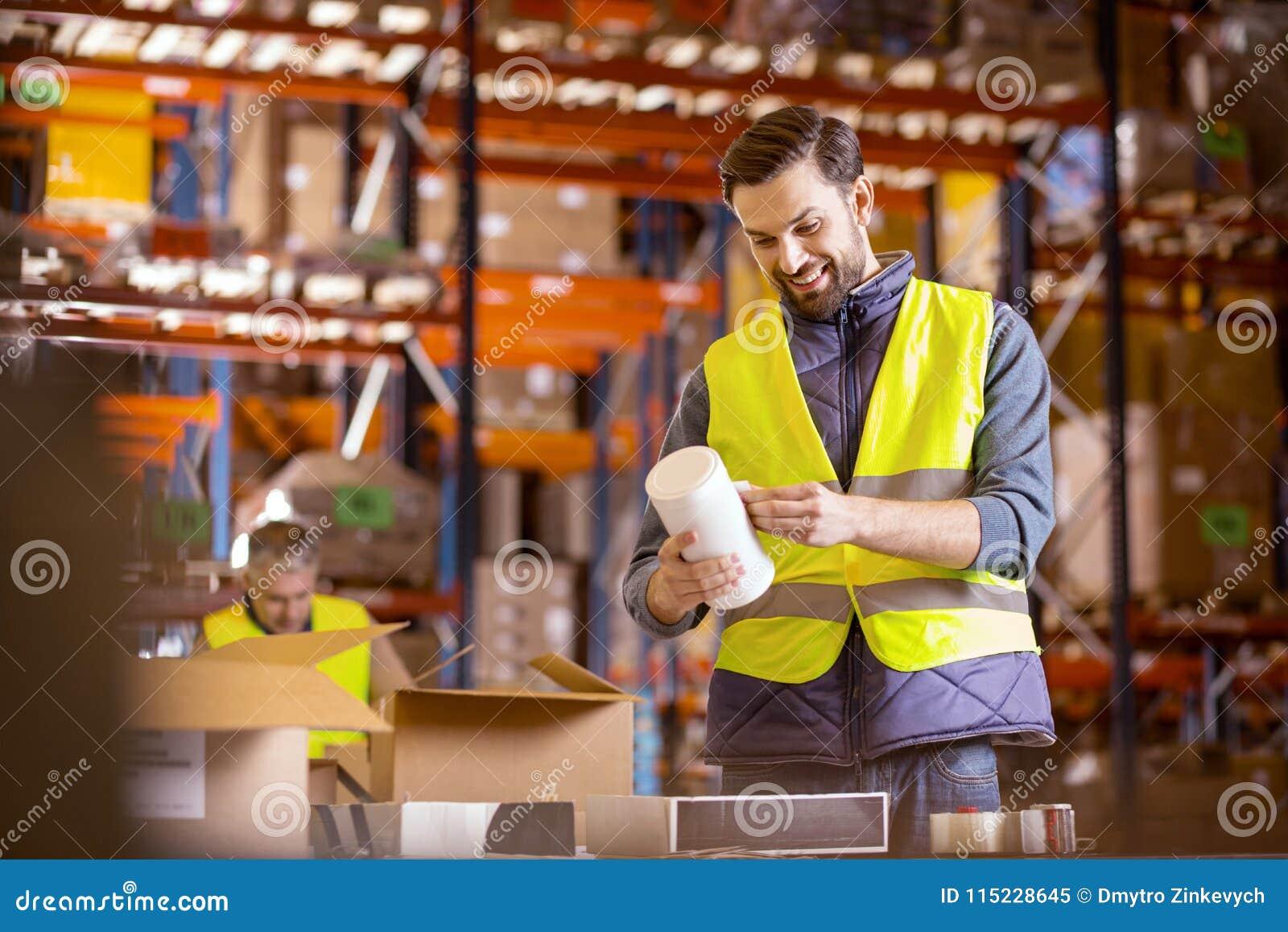 Trabalhador alegre do armazém que põe etiquetas
