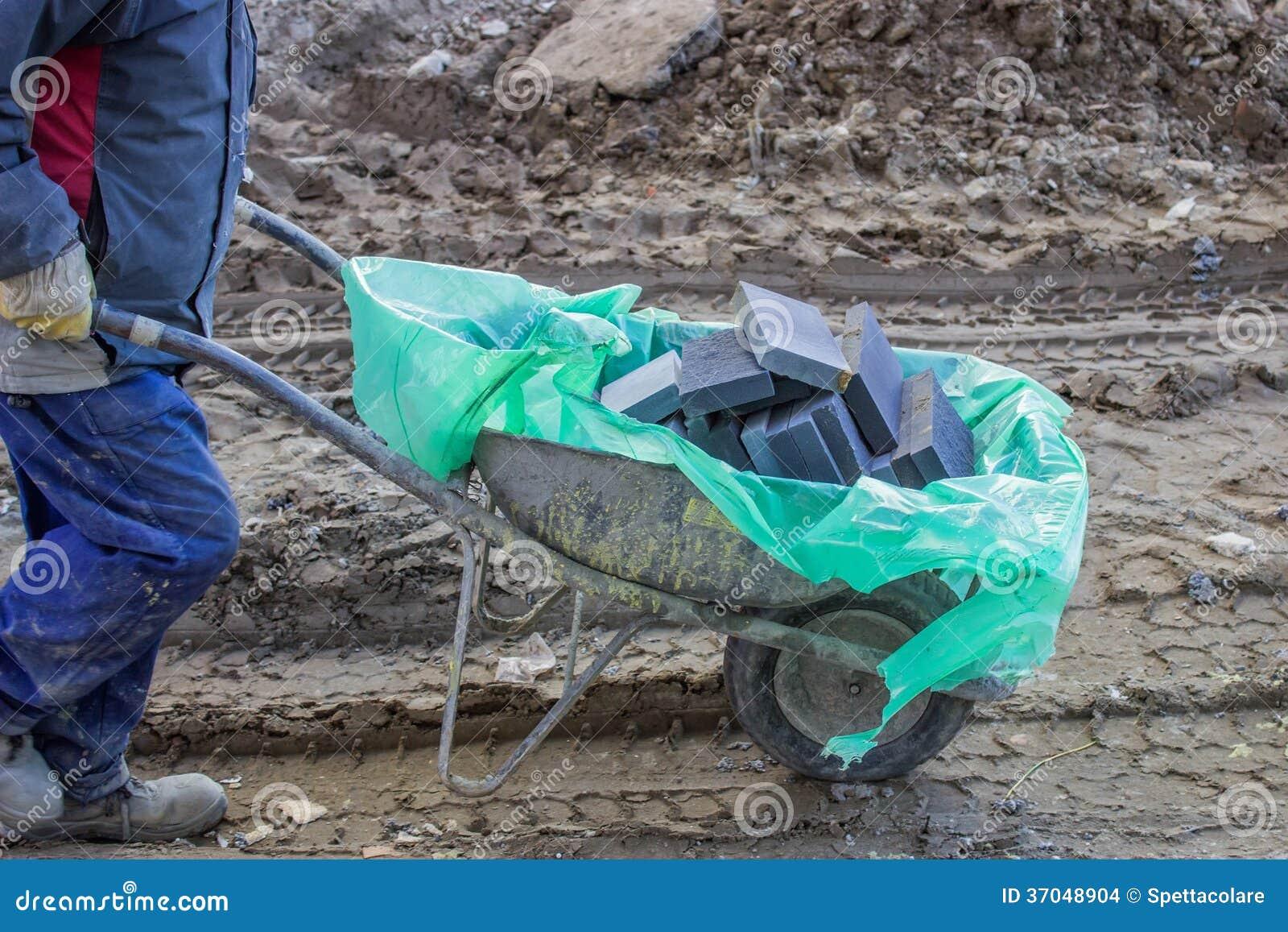 Trabalhador da construção com os tijolos no carrinho de mão