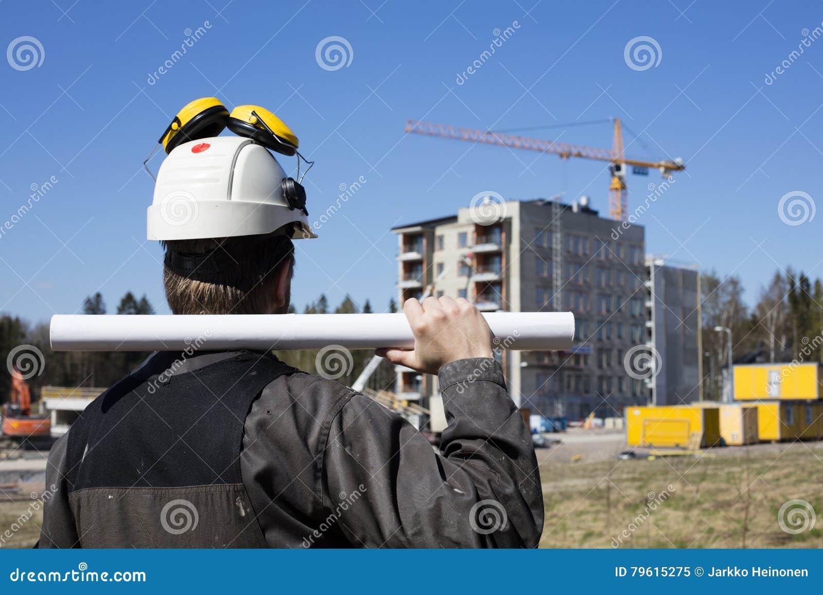 Trabalhador da construção em macacões sujos e um capacete branco em Finlandia