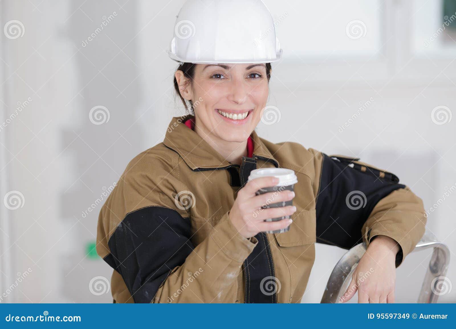 Trabalhador da construção fêmea de sorriso que tem a ruptura de café