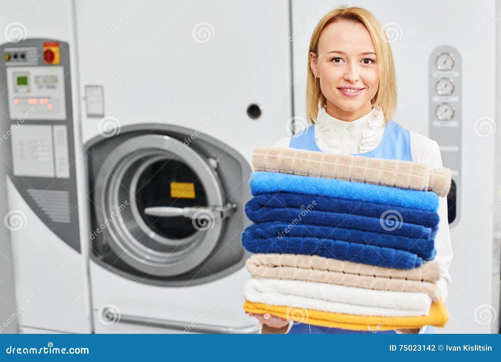 Trabalhador da menina que guarda toalhas limpas de serviço de lavanderia