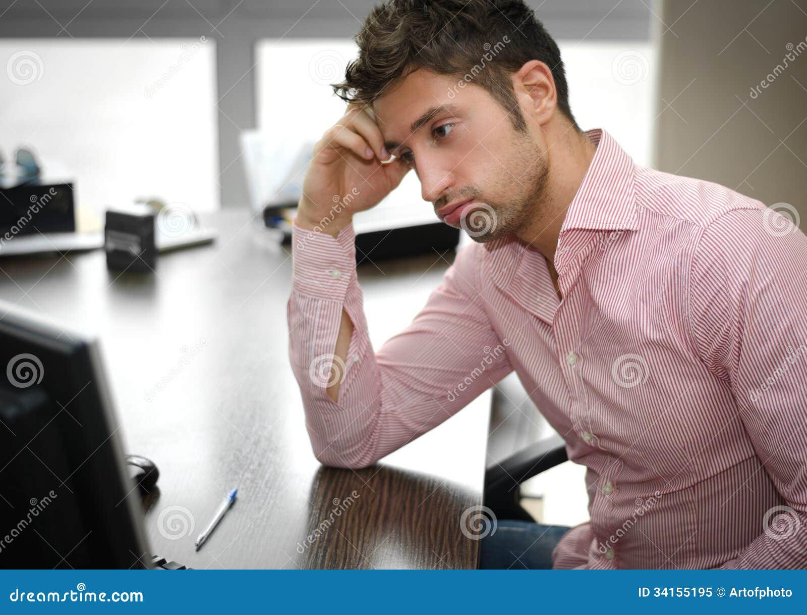 Trabalhador de escritório cansado ou frustrante que olha o ecrã de computador