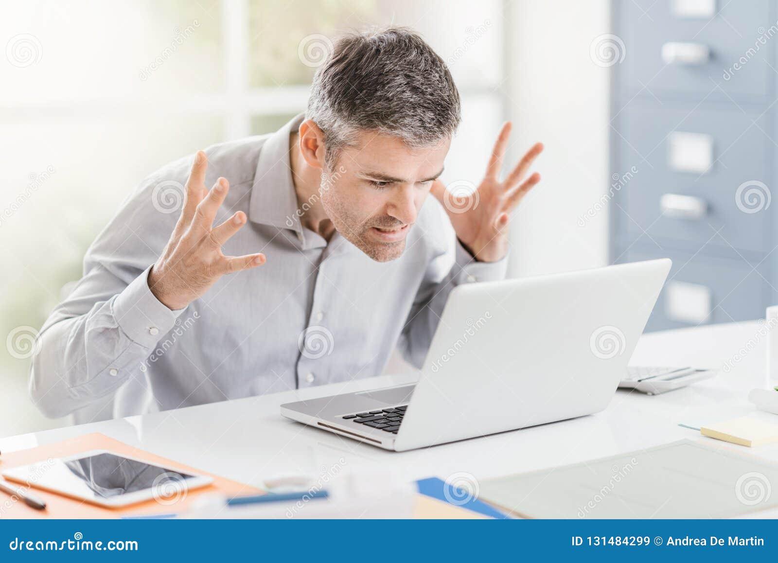 Trabalhador de escritório frustrante irritado que tem problemas com seus portátil e conexão, problemas do computador e pesquisand