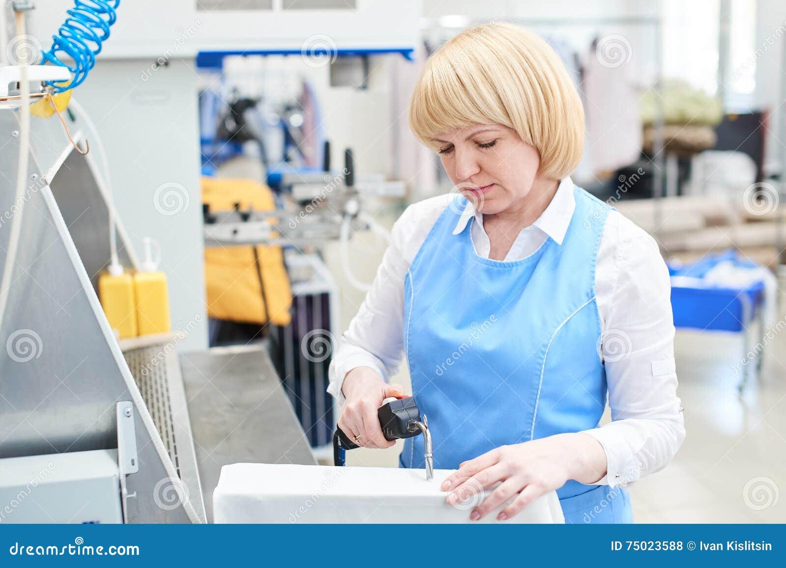 Trabalhador de mulher na remoção de mancha do processo da lavanderia