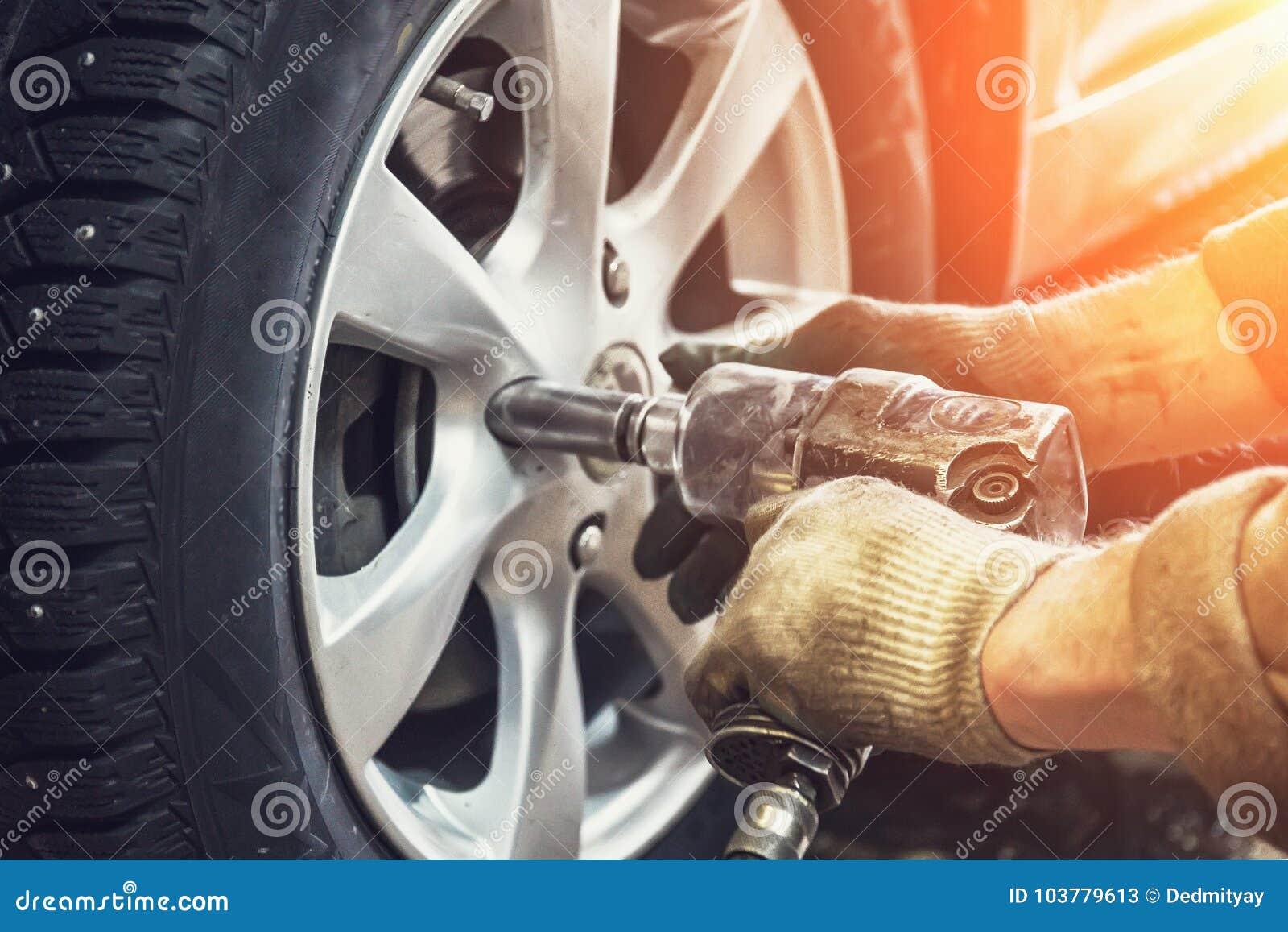 Trabalhador do mecânico de carro que faz a substituição do pneu ou da roda com a chave pneumática na garagem da estação do serviç