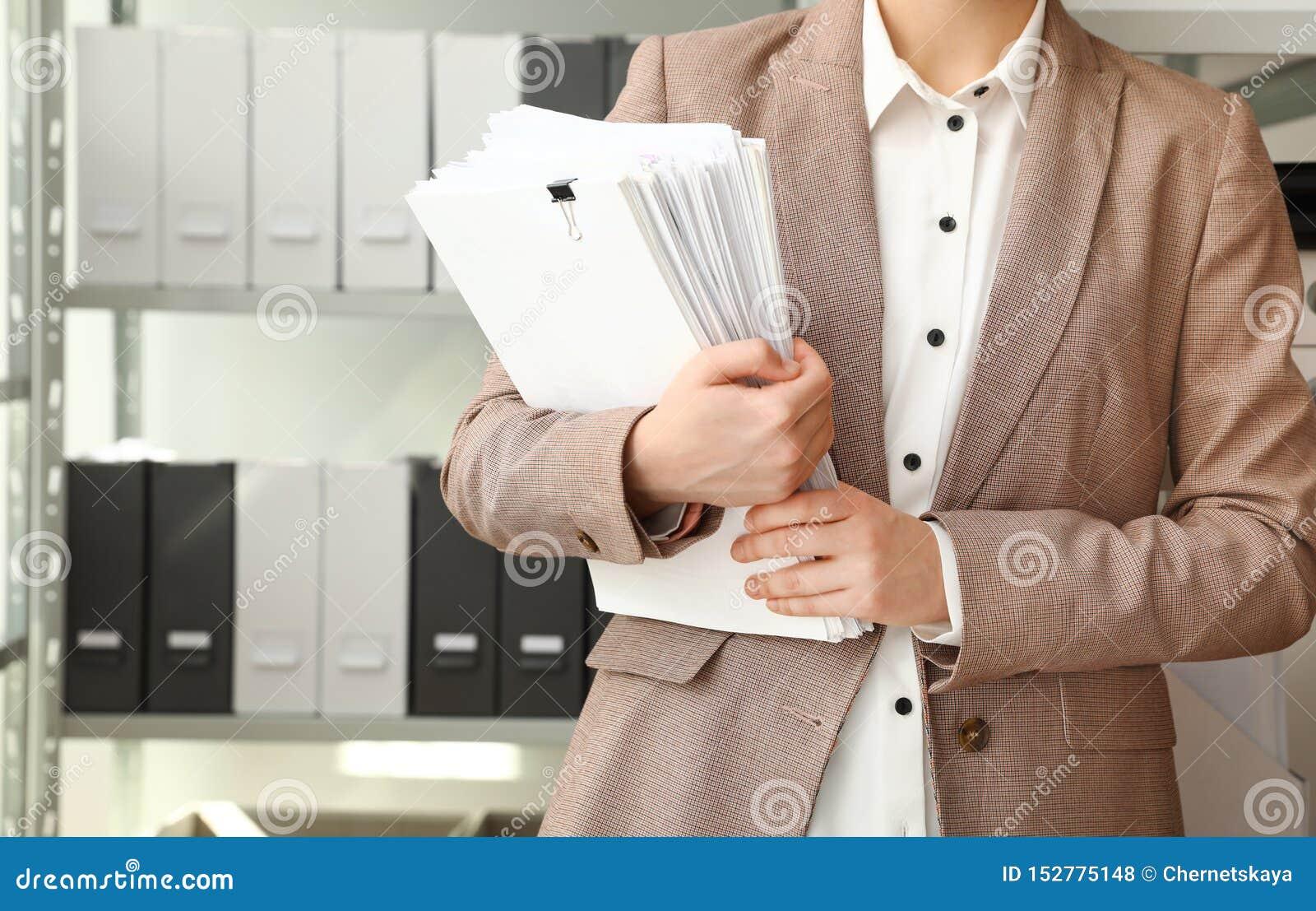 Trabalhador fêmea com documentos no arquivo, close up